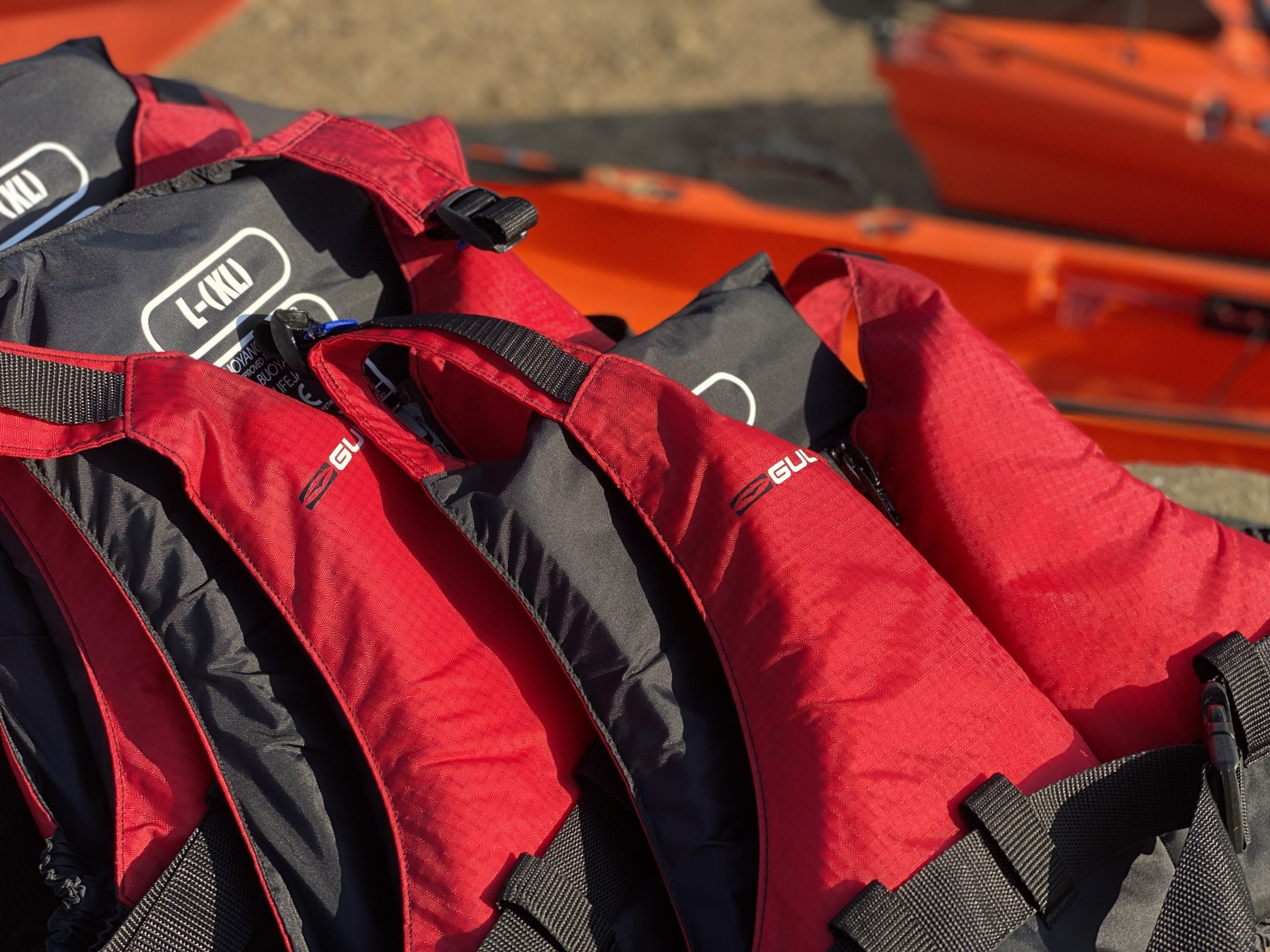 Red buoyancy aids lined up ready for use with Orange kayaks in the background.