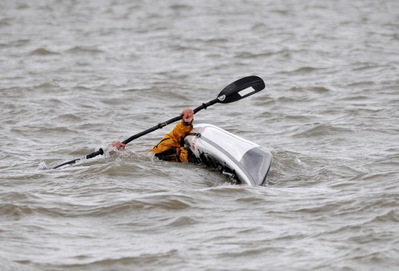 Sea kayaker doing an eskimo roll in deep water.
