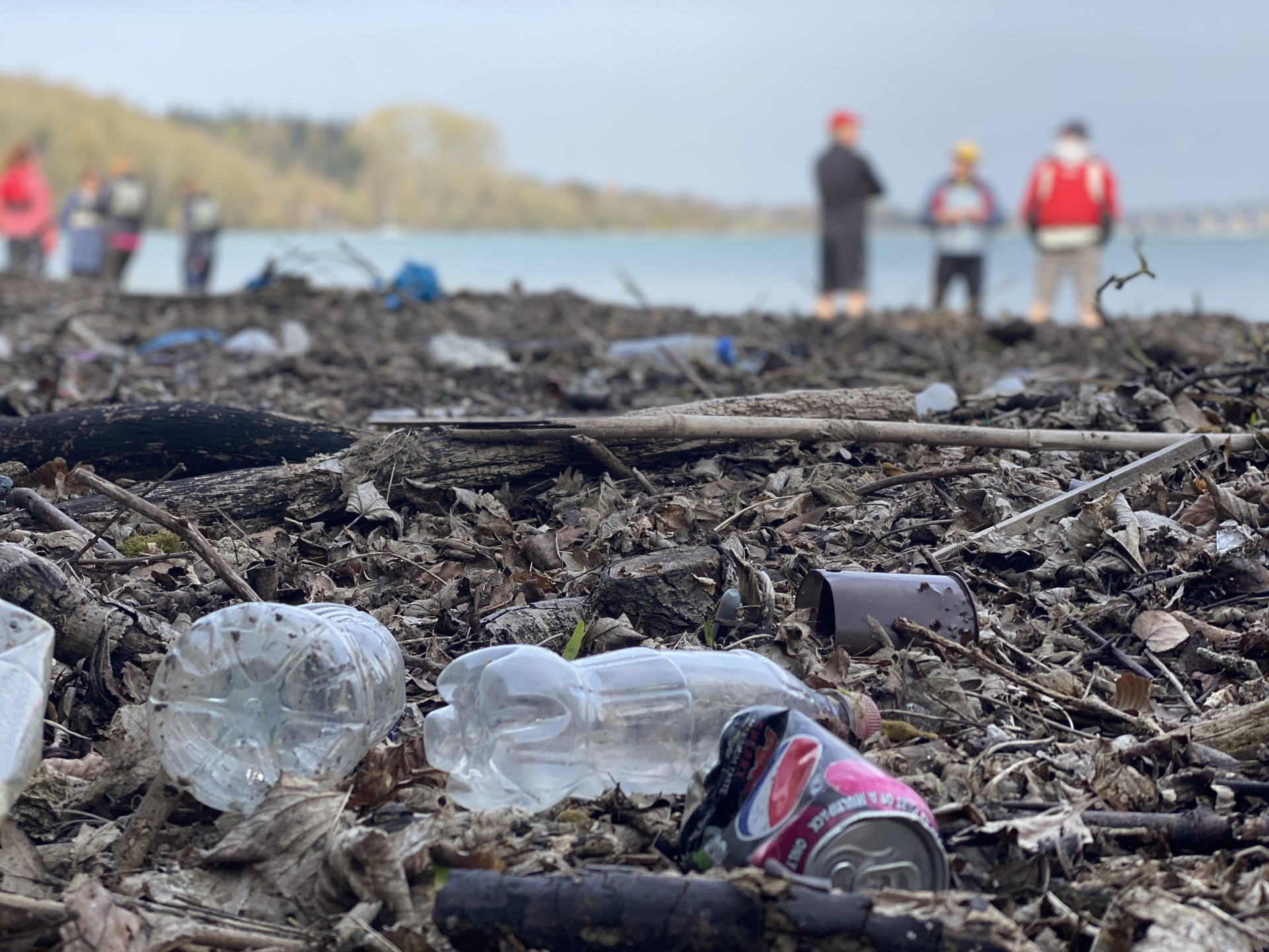 Plastic bottles and tins lying on a beach with kayakers in the background.