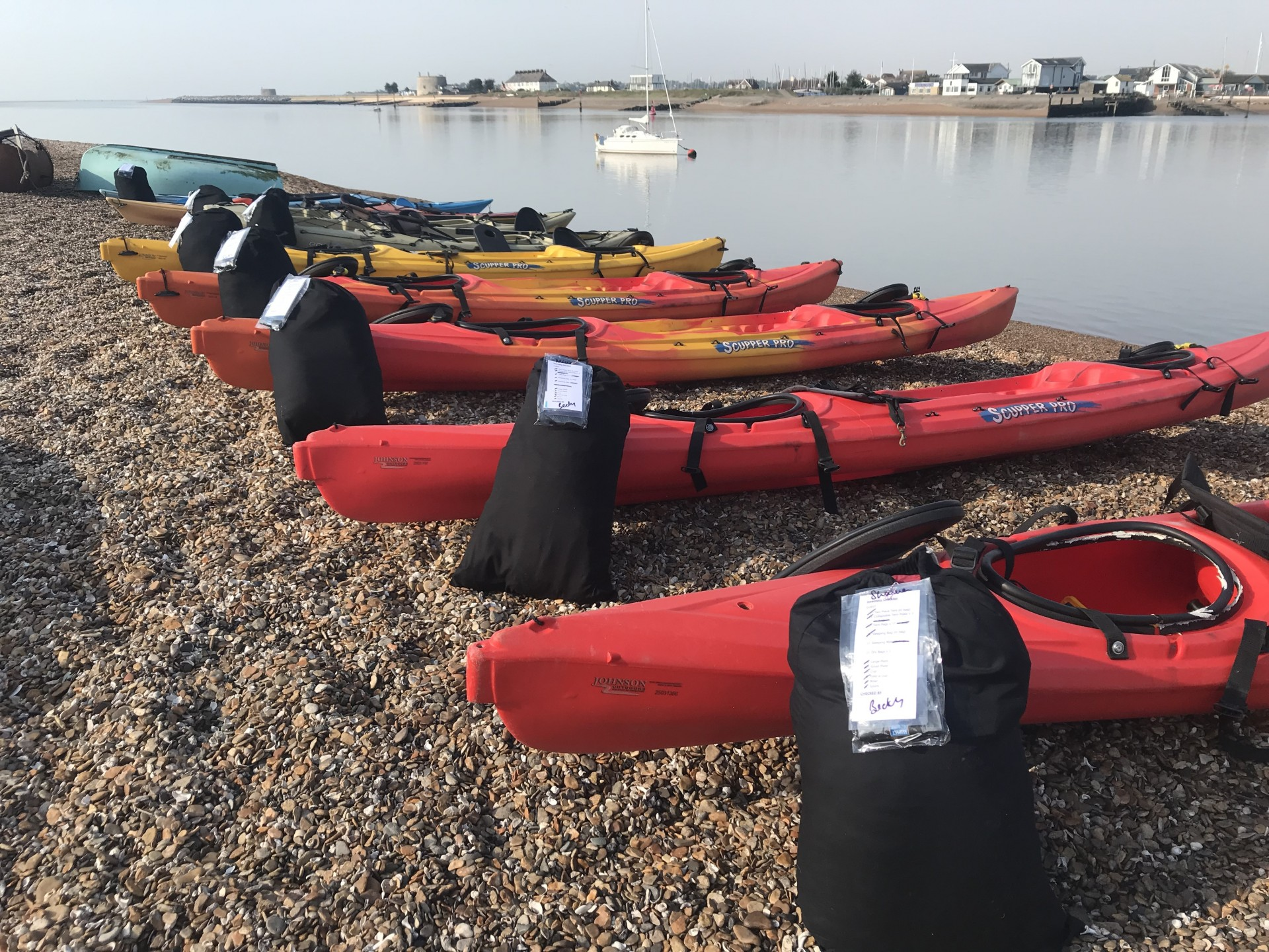 All inclusive wild camping events with kayaks lined up with bags of equipment for each guest