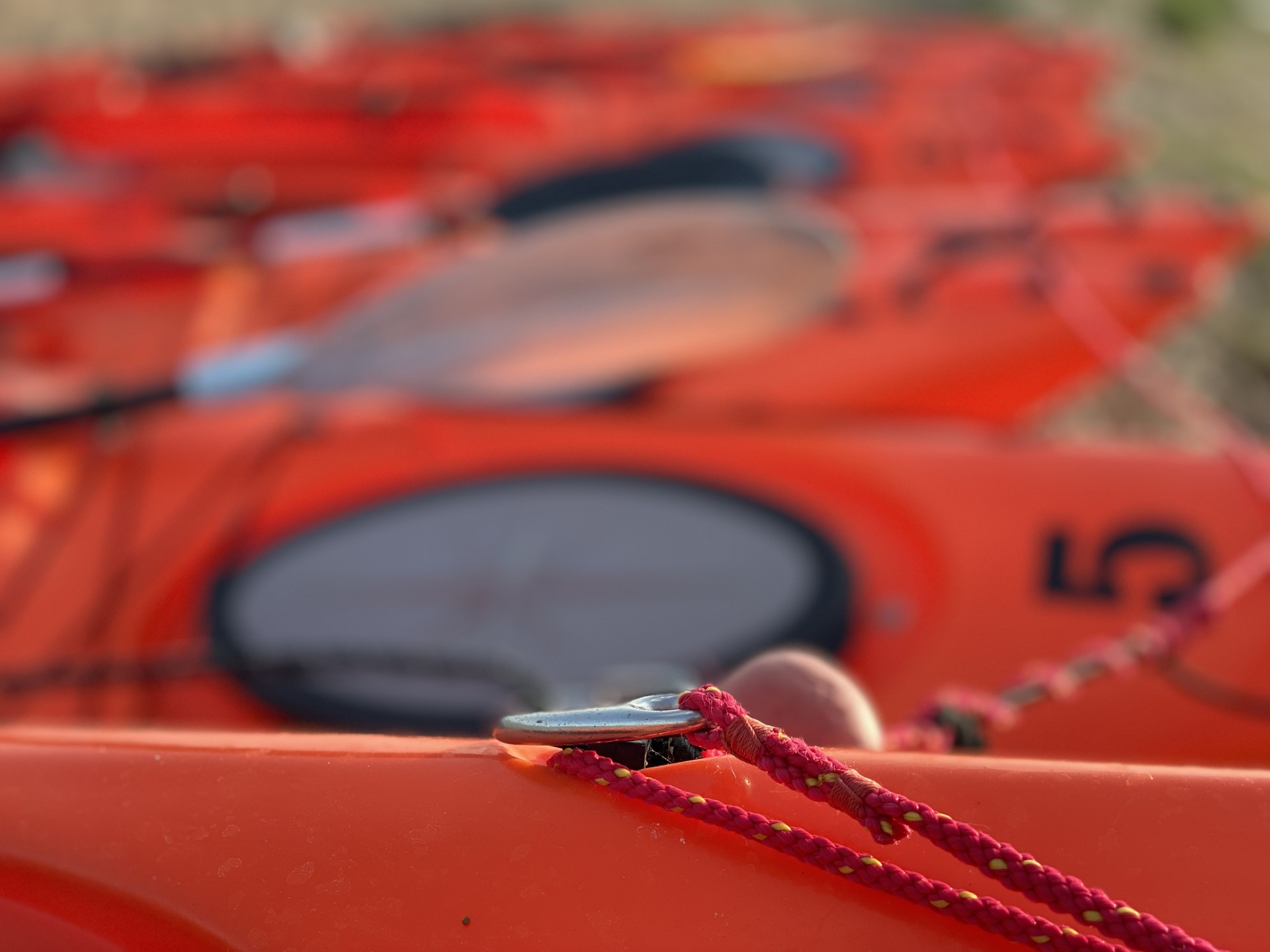 A long line of orange sit-on-top kayaks