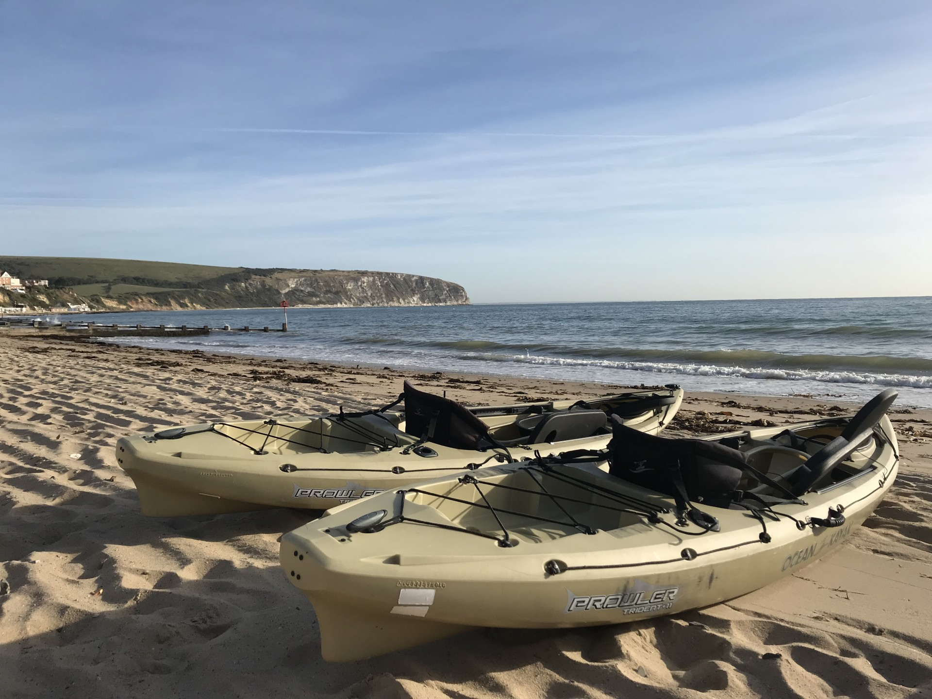 Two Ocean Kayak Prowler sit-on-top kayaks on a sandy beach in Swanage.