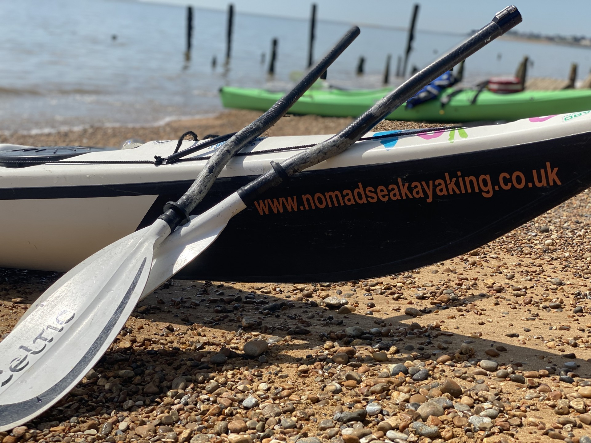 A white Celtic paddle split in two & resting on a sea kayak with another sea kayak in the background