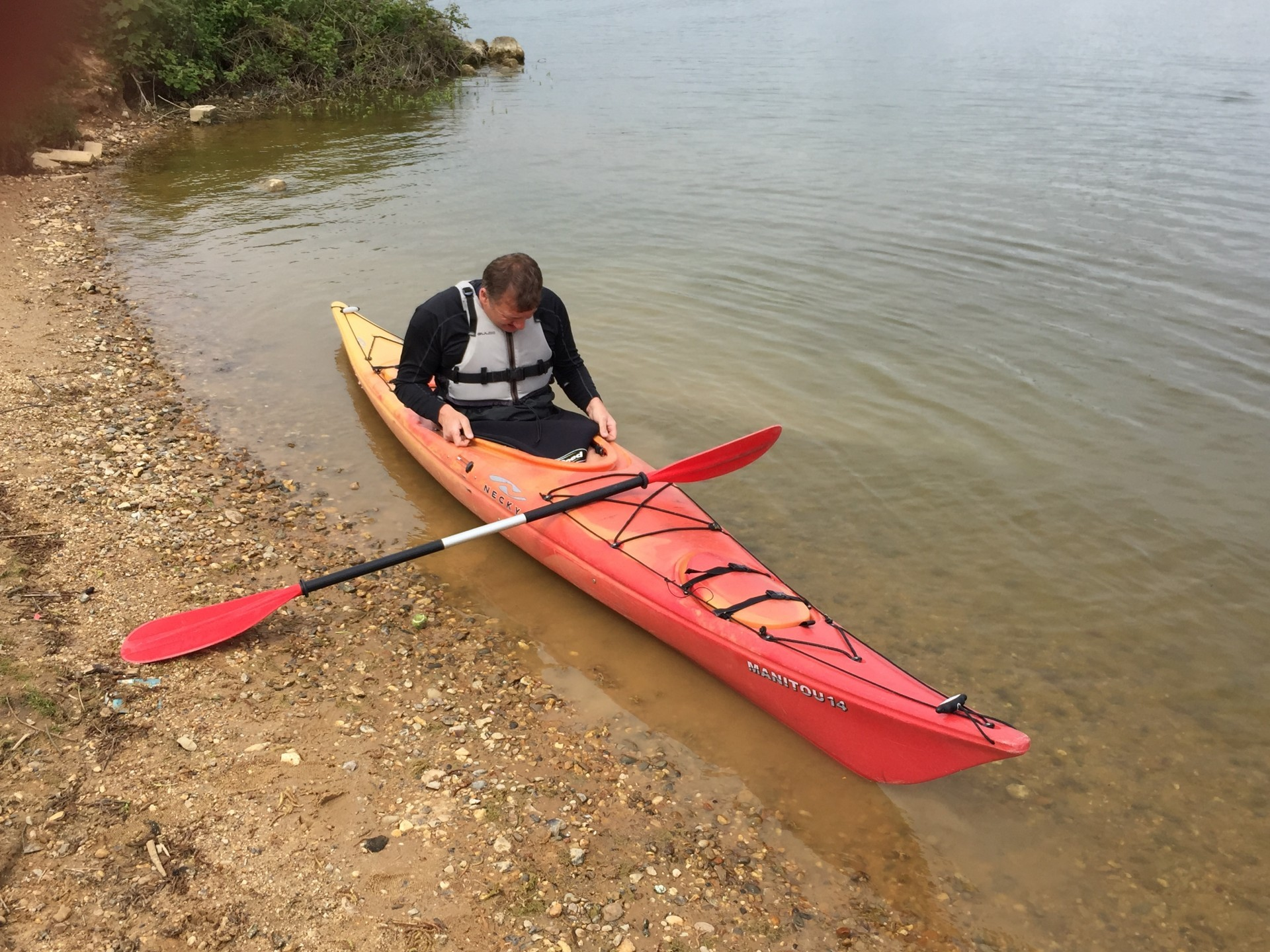 A red touring kayak being launched in flat water