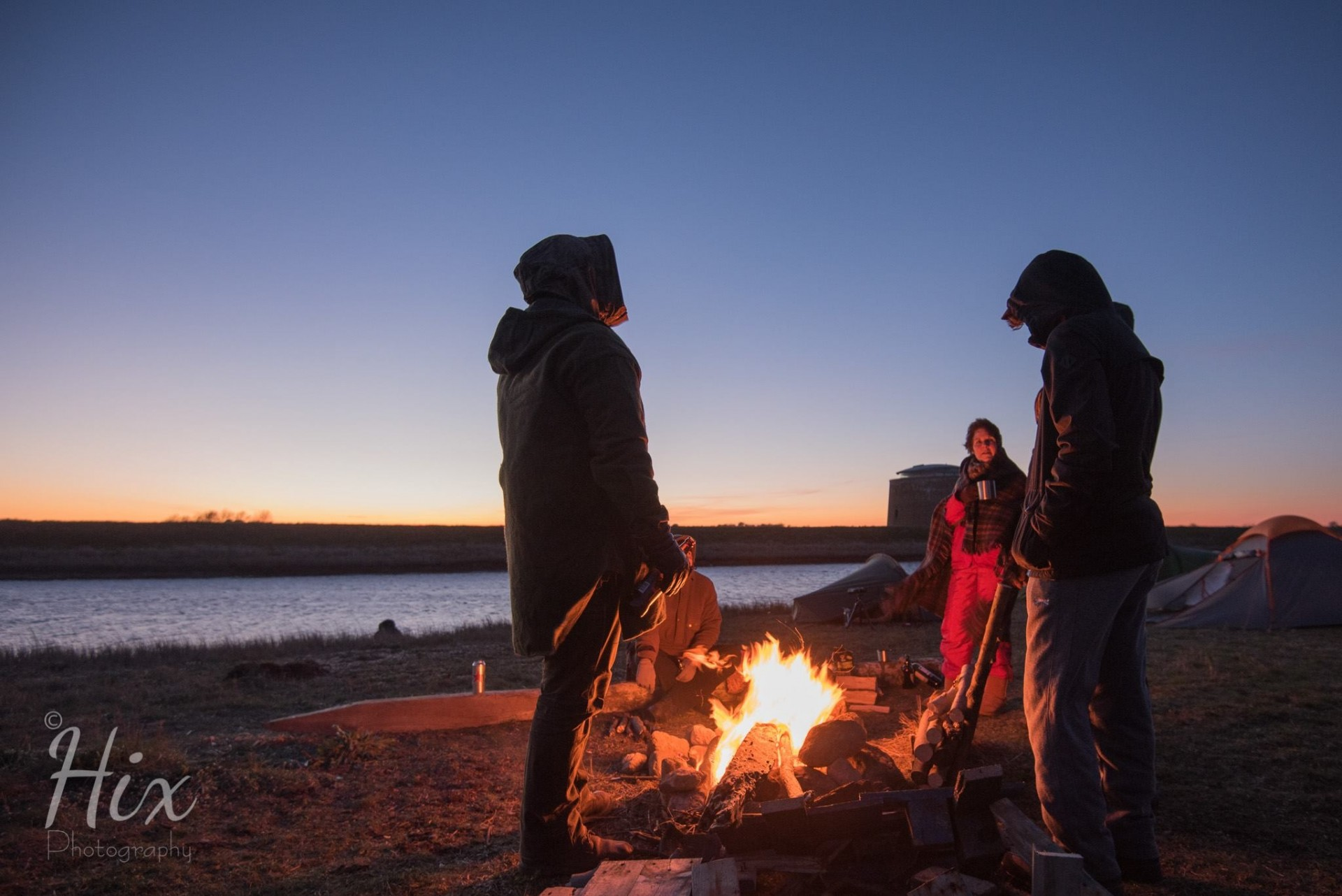 Warm around the fire at sunset on a wild camp