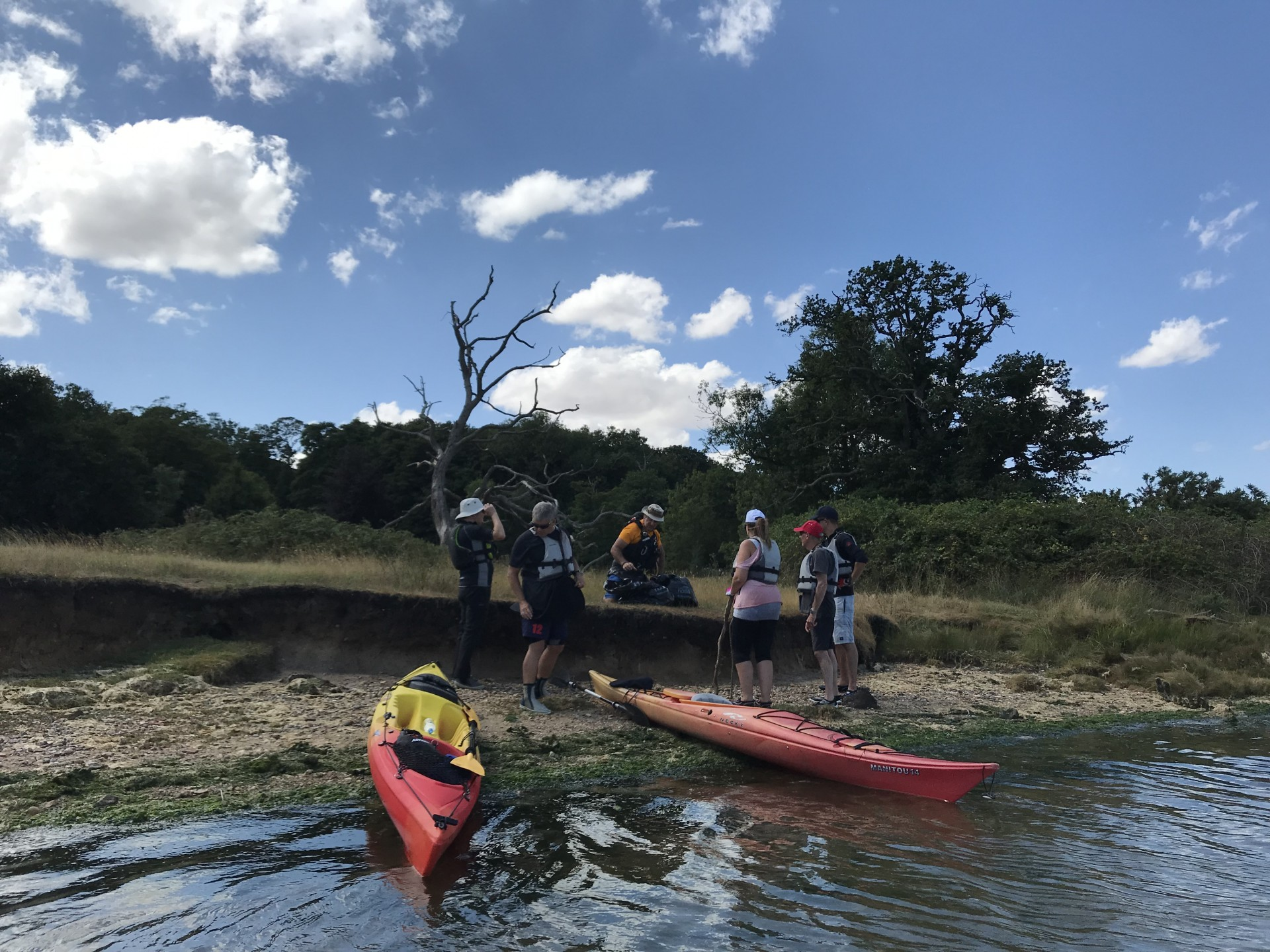 Two kayaks beached wih a small group collecting refuse
