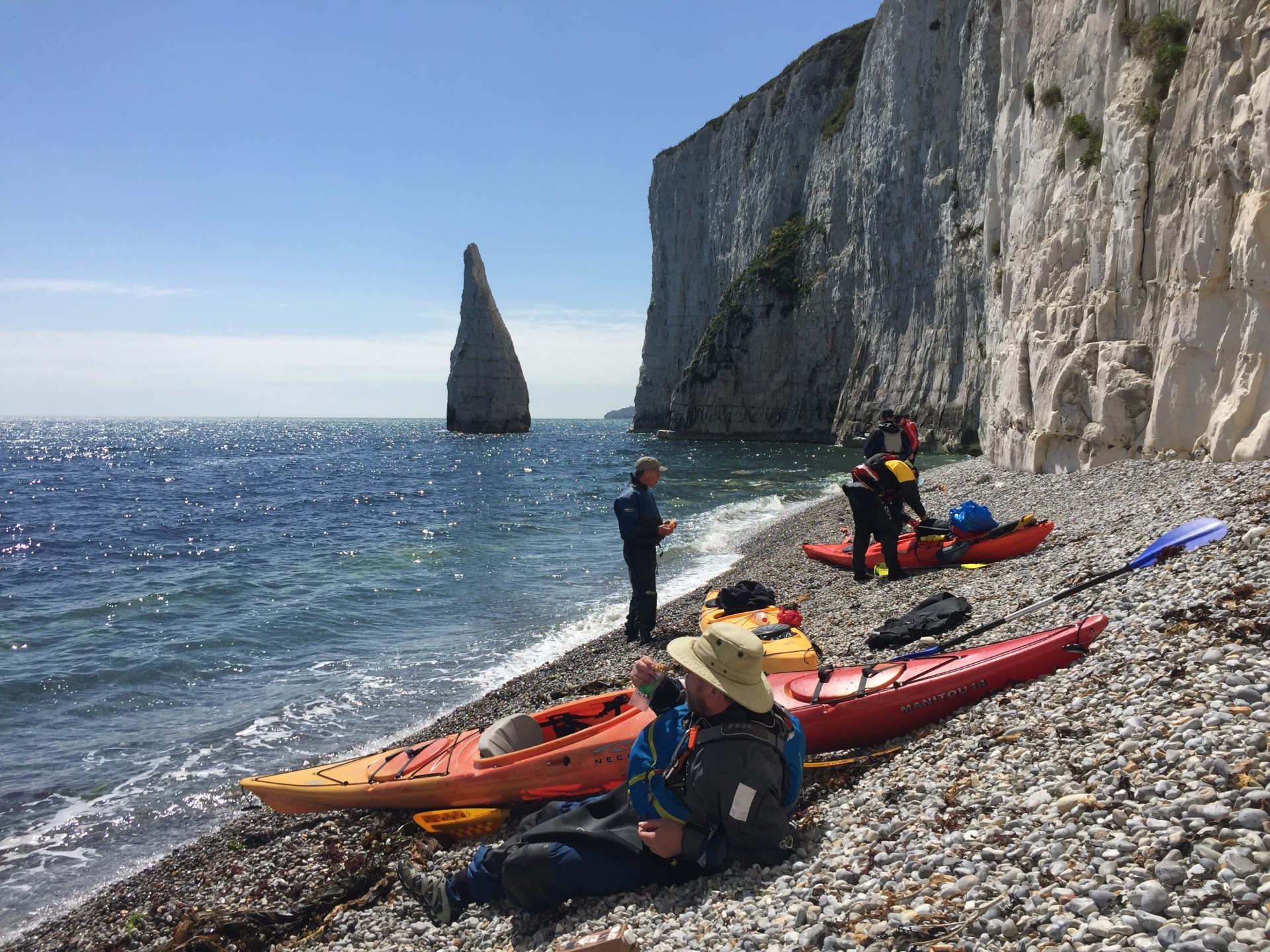 Kayakers sitting on a shingle beach near Old Harry rocks, Swanage, Dorset coast