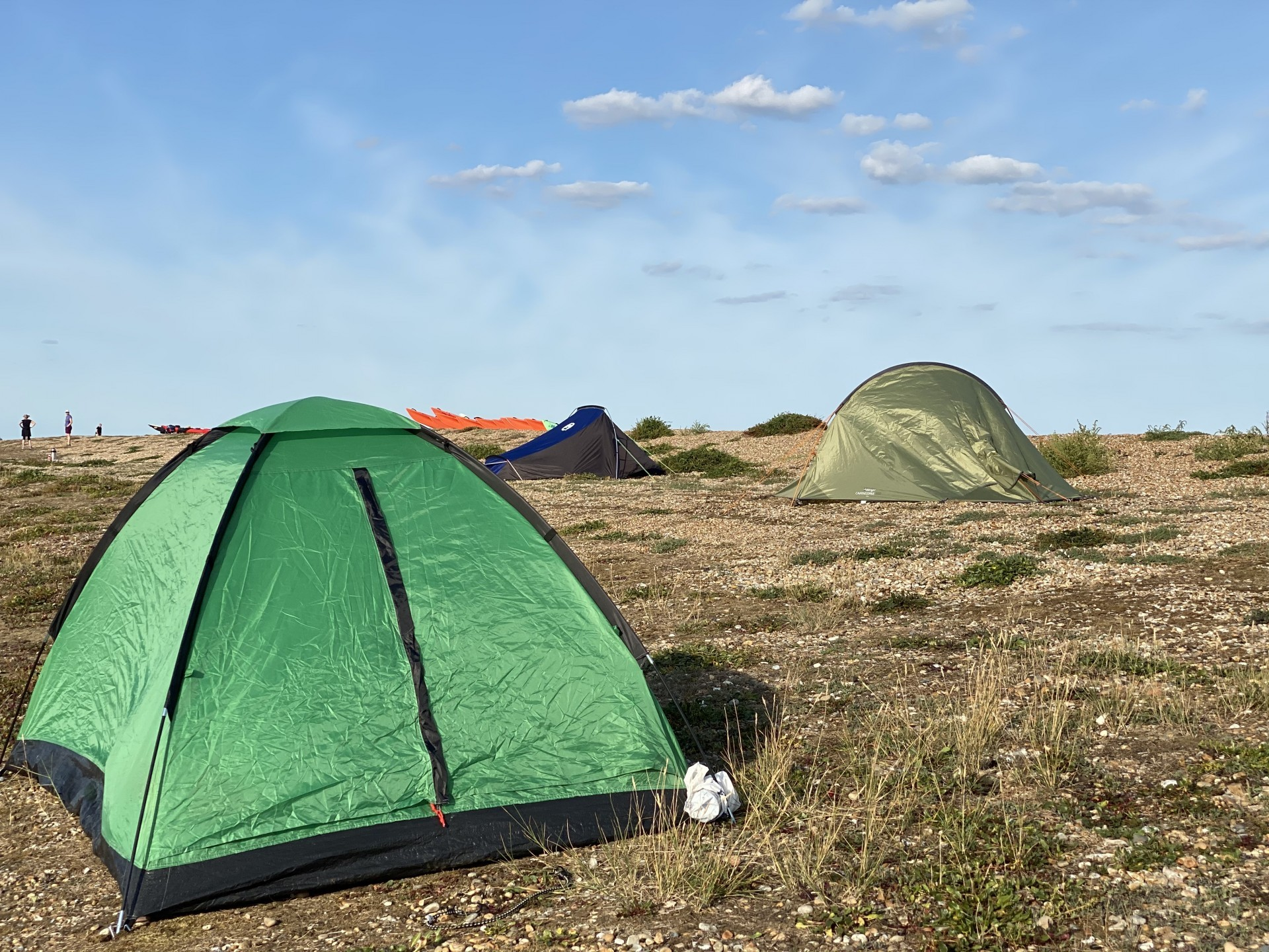 Green tents pitched neatly on beach wild camping and kayaking sea kayak trips in Suffolk and Essex