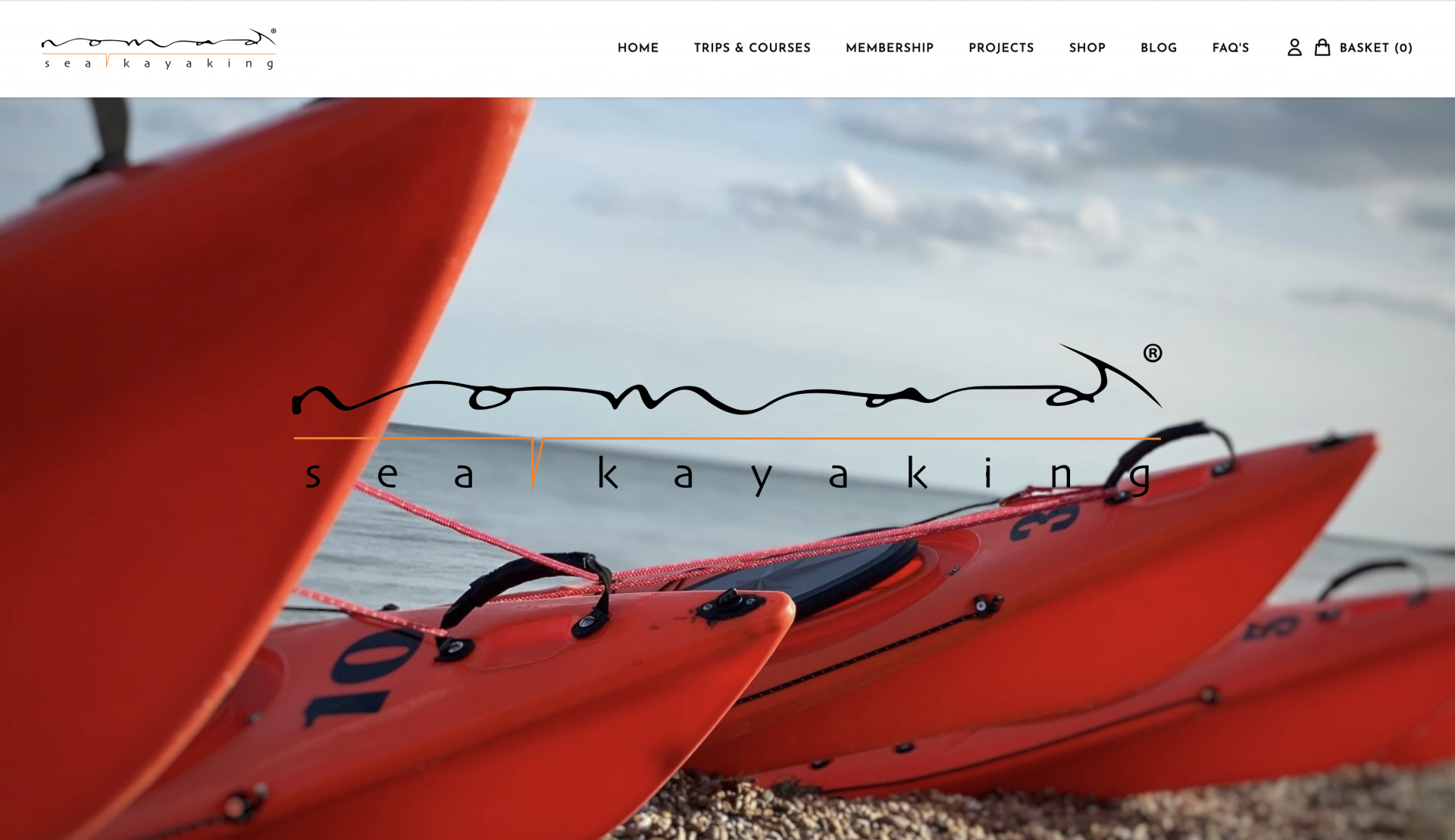 /storage/Home page of the new web site showing matching orange kayaks lined up on a shingle beach with blue skies in the background.
