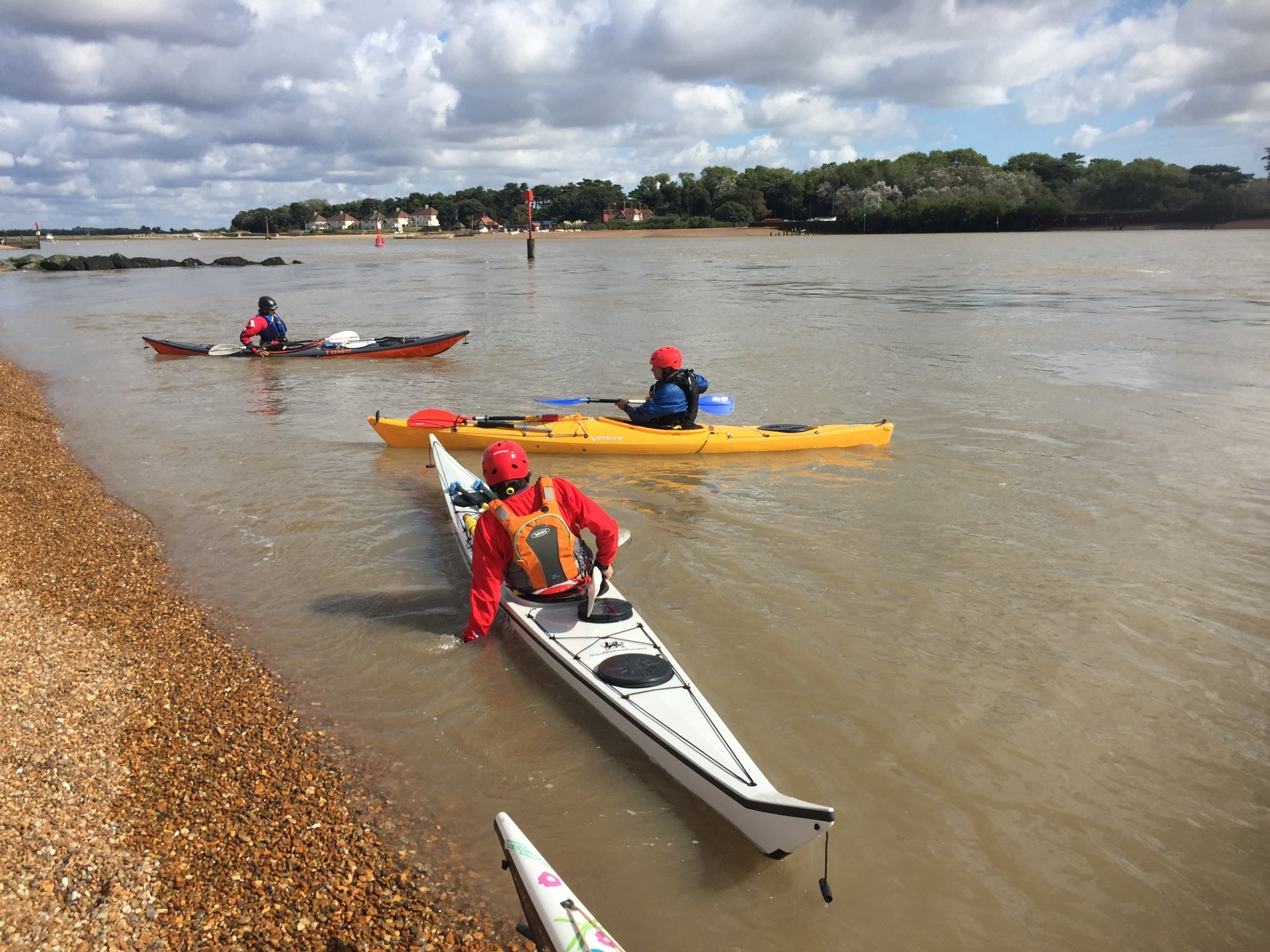 Sea kayakers launching in flat calm tidal conditions at the mouth of the Deben estuary.