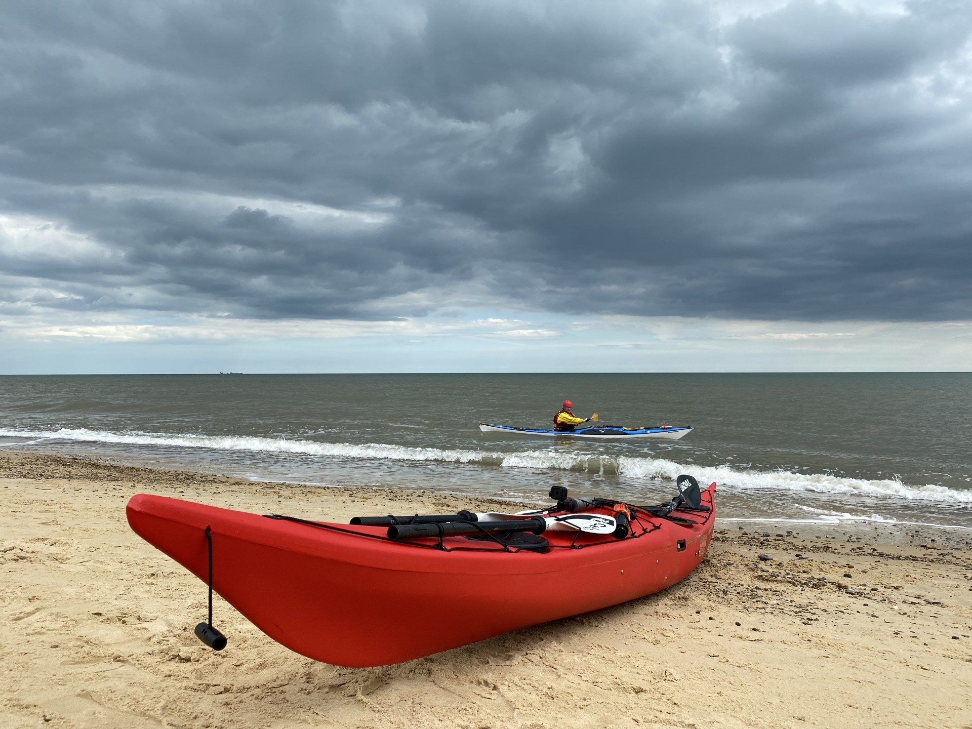 NDK RM Sport plastic sea kayak in red on a sandy beach with a paddler in the background