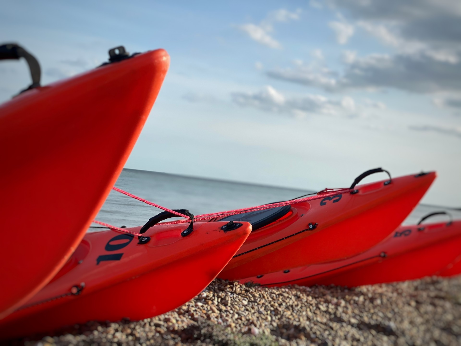 Orange kayaks on a shingle beach tethered together