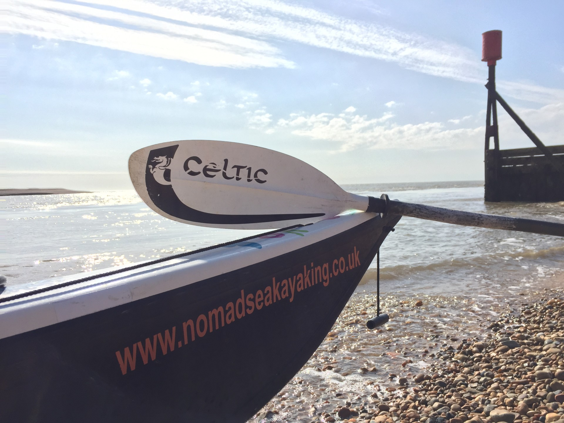 A sea kayak with the name NOMAD Sea Kayaking emblazoned on its bow.