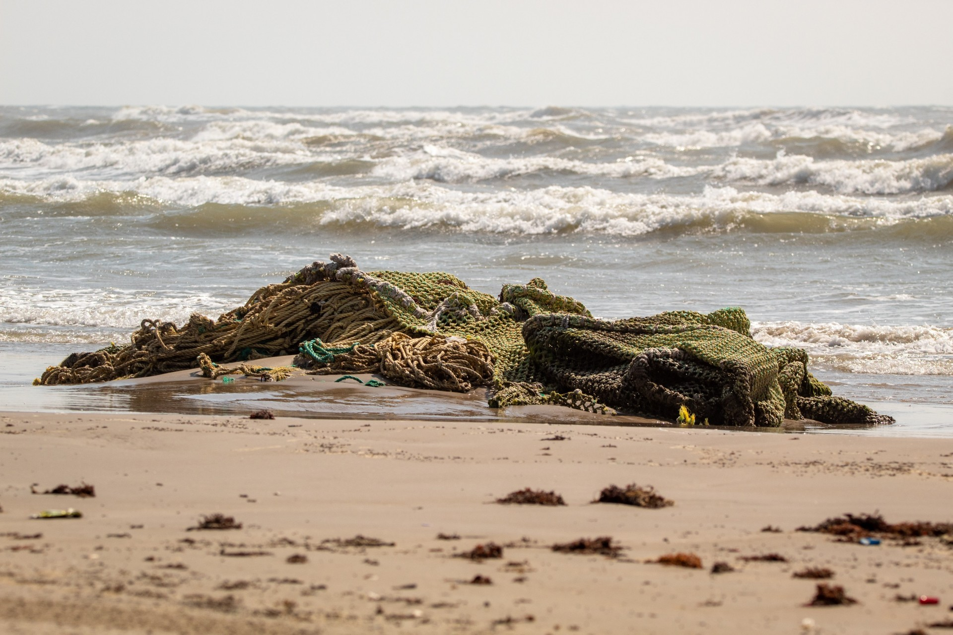 A huge pile of discarded fishing nets washed up on a beach
