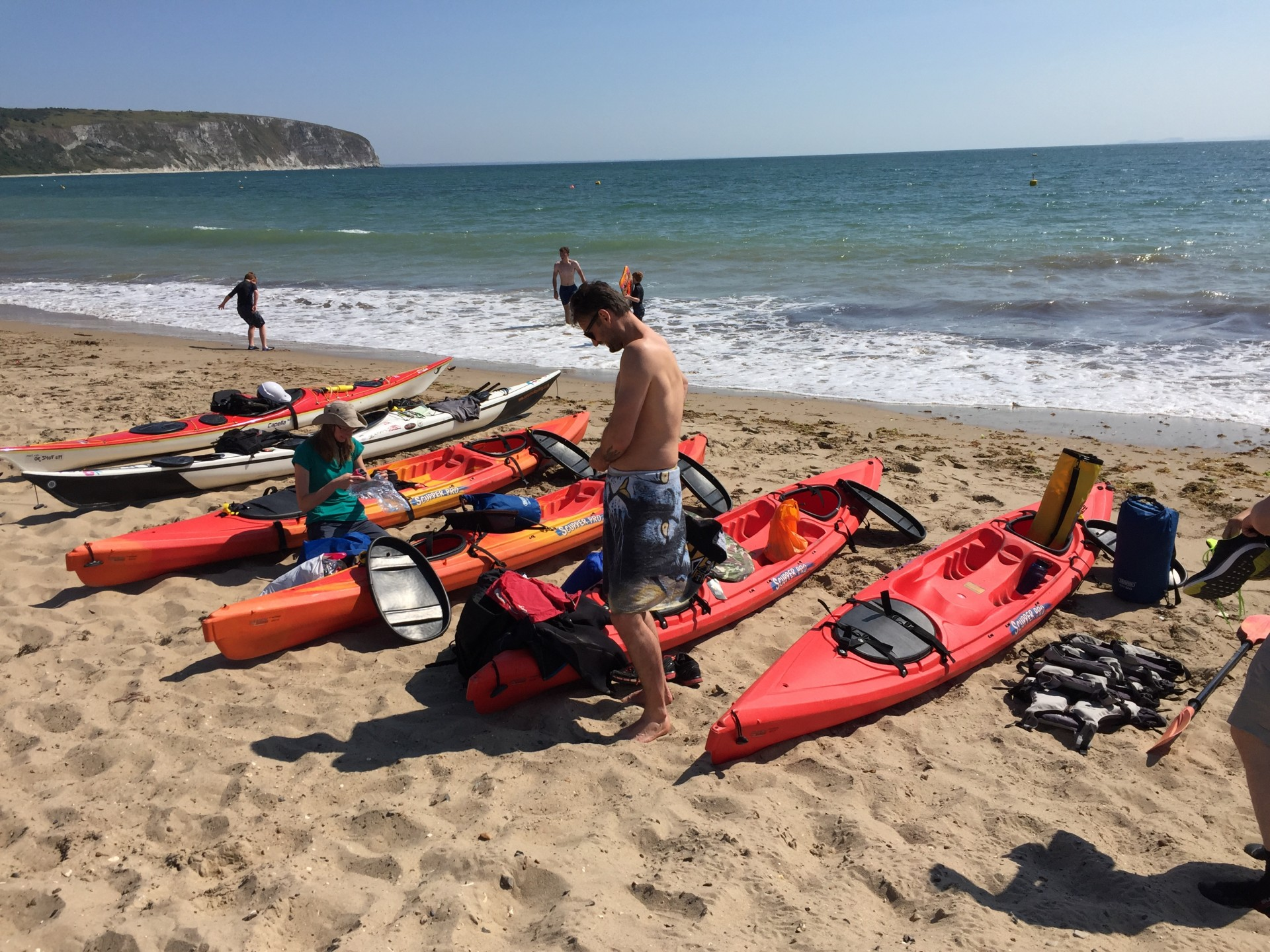 Kayaks line a sandy beach on the Dorset Jurassic coast