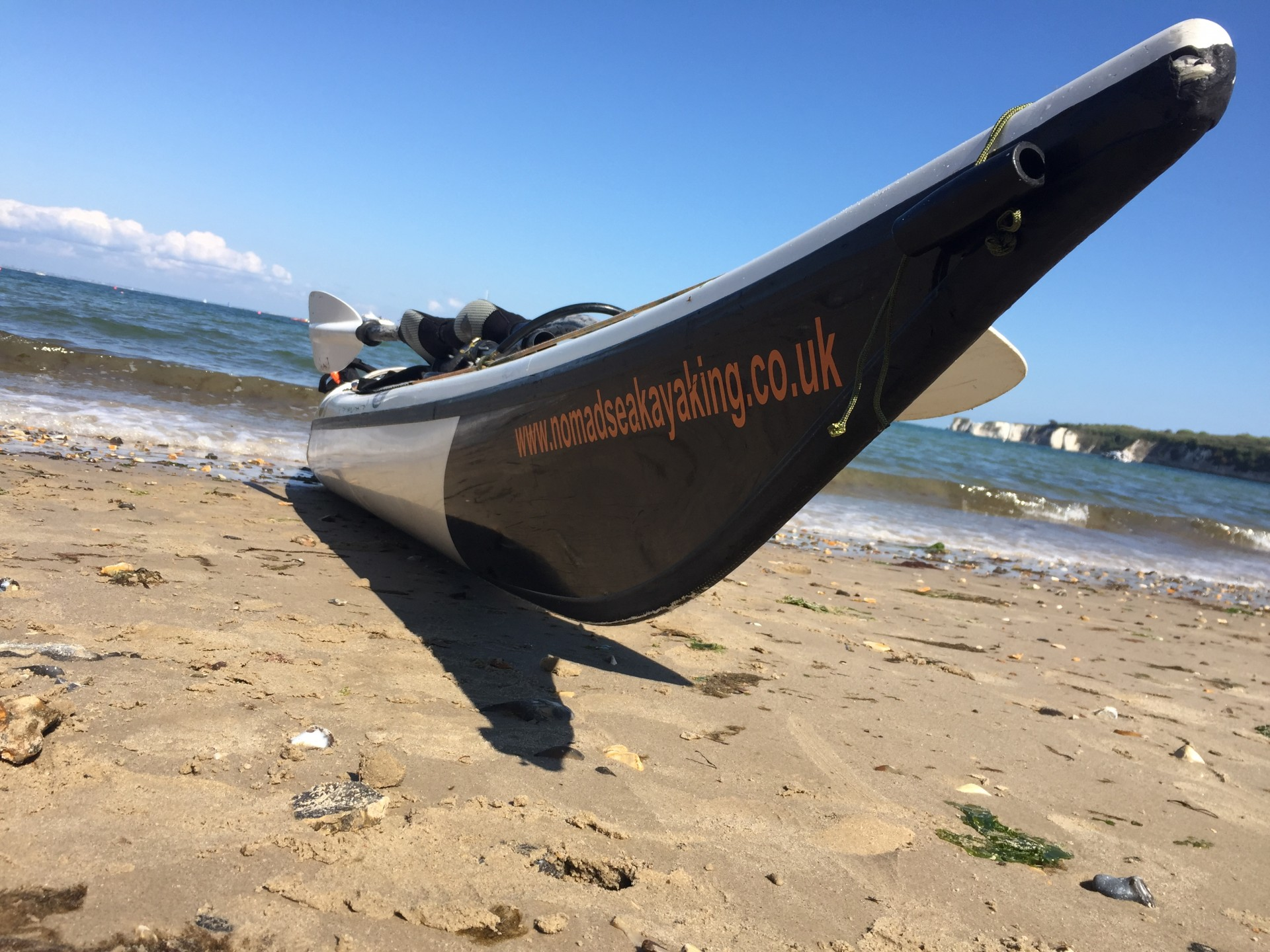 A sea kayak on a sandy beach with blue skies.