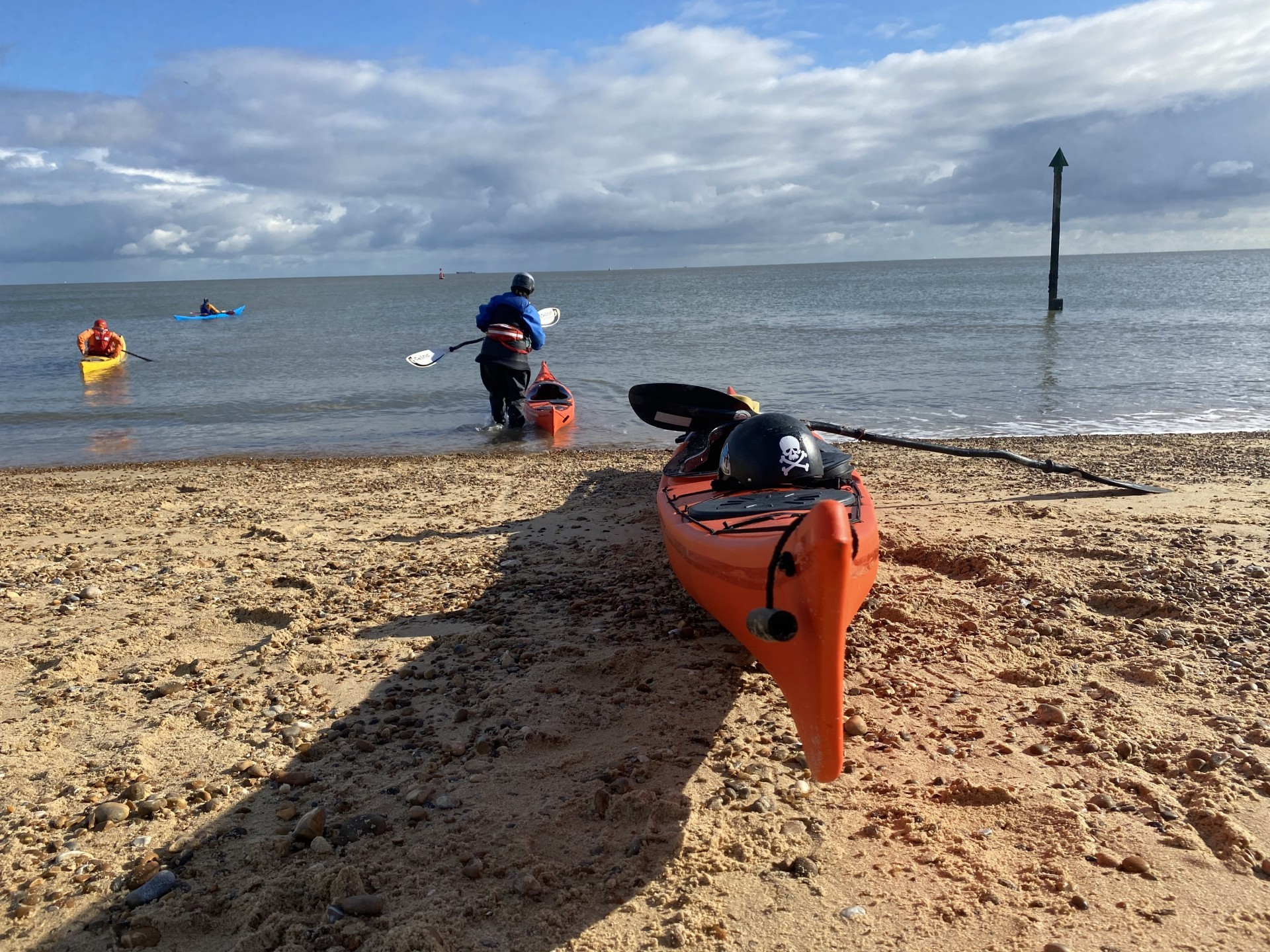 Sea kayakers launching in flat, calm sea conditions