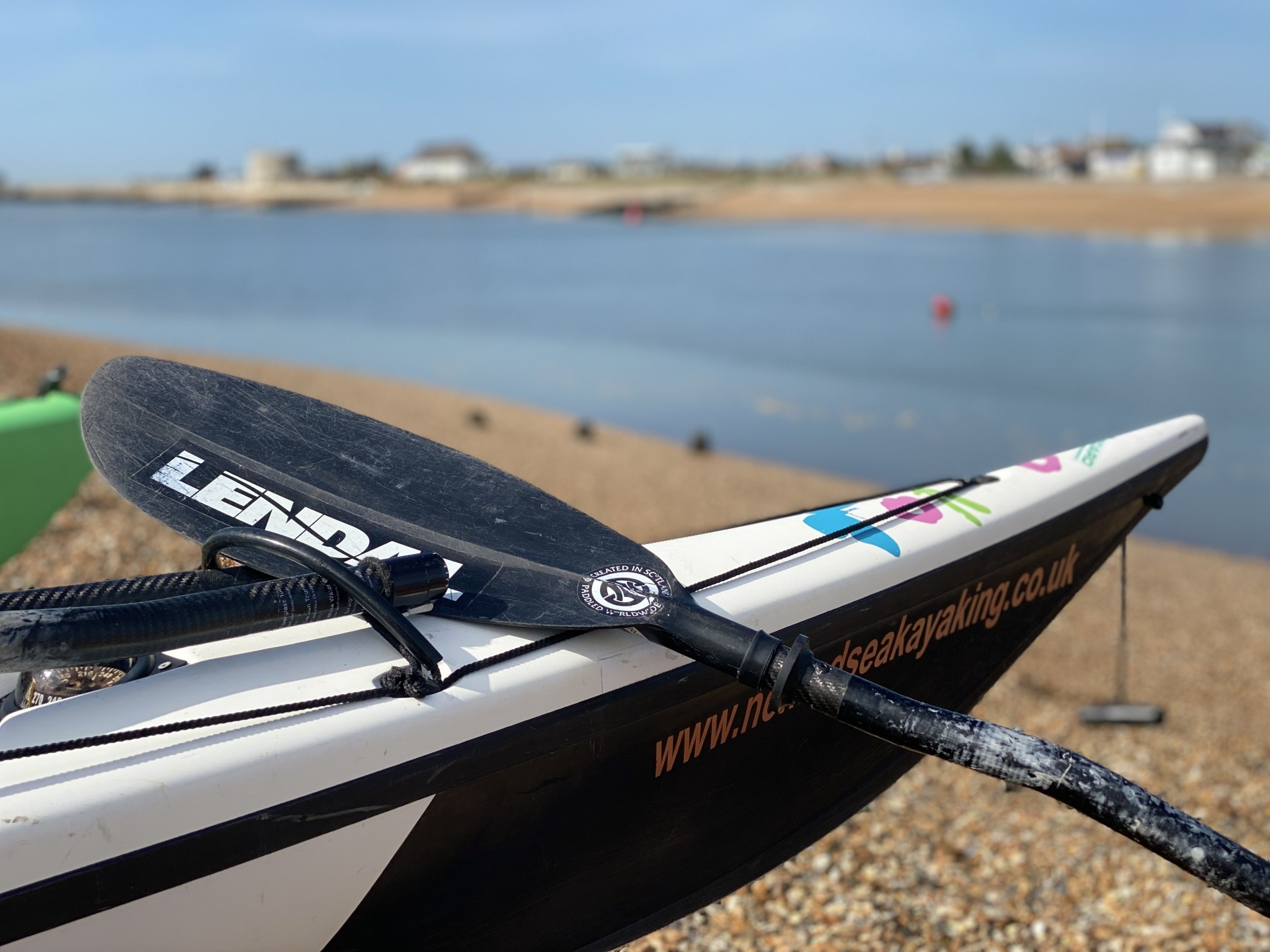 A black carbon fibre Lendal paddle resting against a sea kayak on a beautiful shingle beach