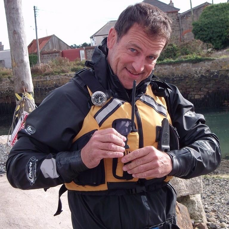 Sea kayak guide buckling his buoyancy aid