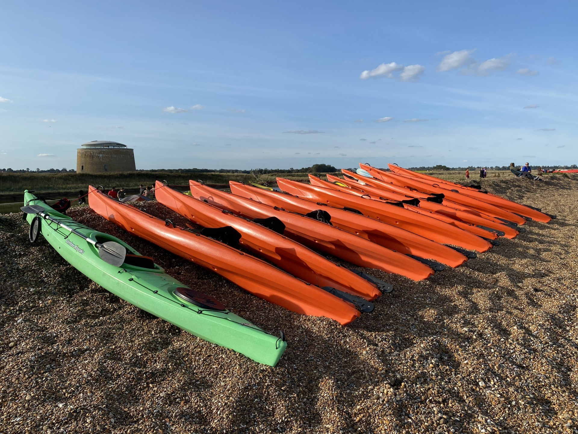 Sit-on-top and touring kayaks lines up on a shingle beach in Suffolk