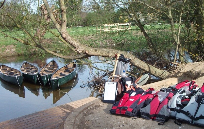 Four large canoes tethered to a tree on a river