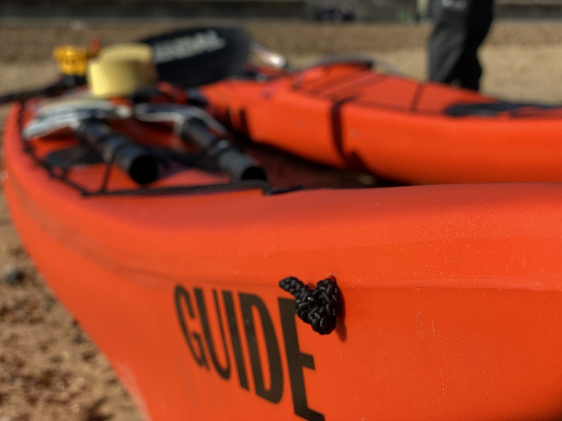 A sea kayak clearly showing the word 'Guide' on the bow.