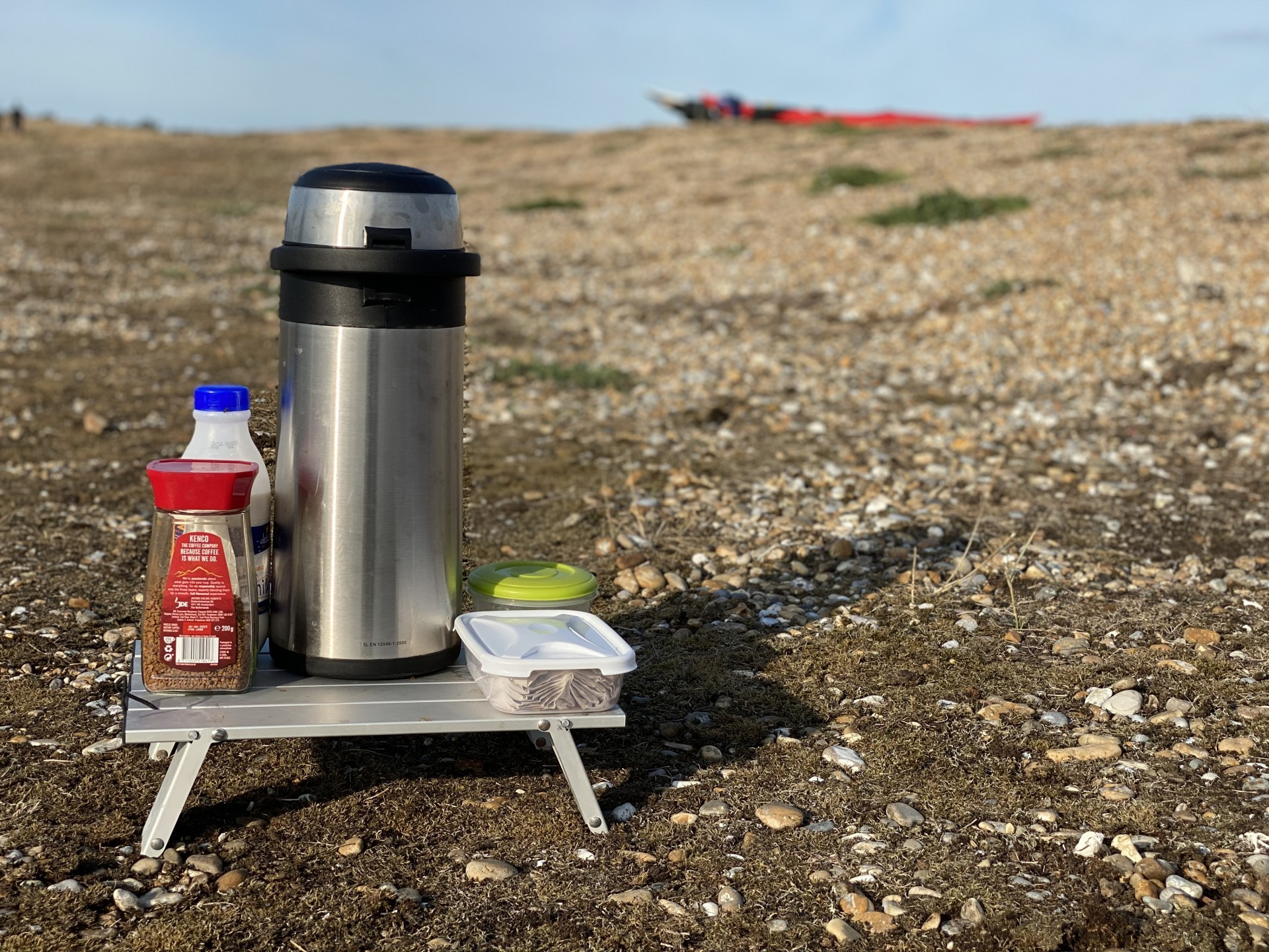 Hot water flask with supplies on a shingle beach as part of the all inclusive Suffolk wild camping trips
