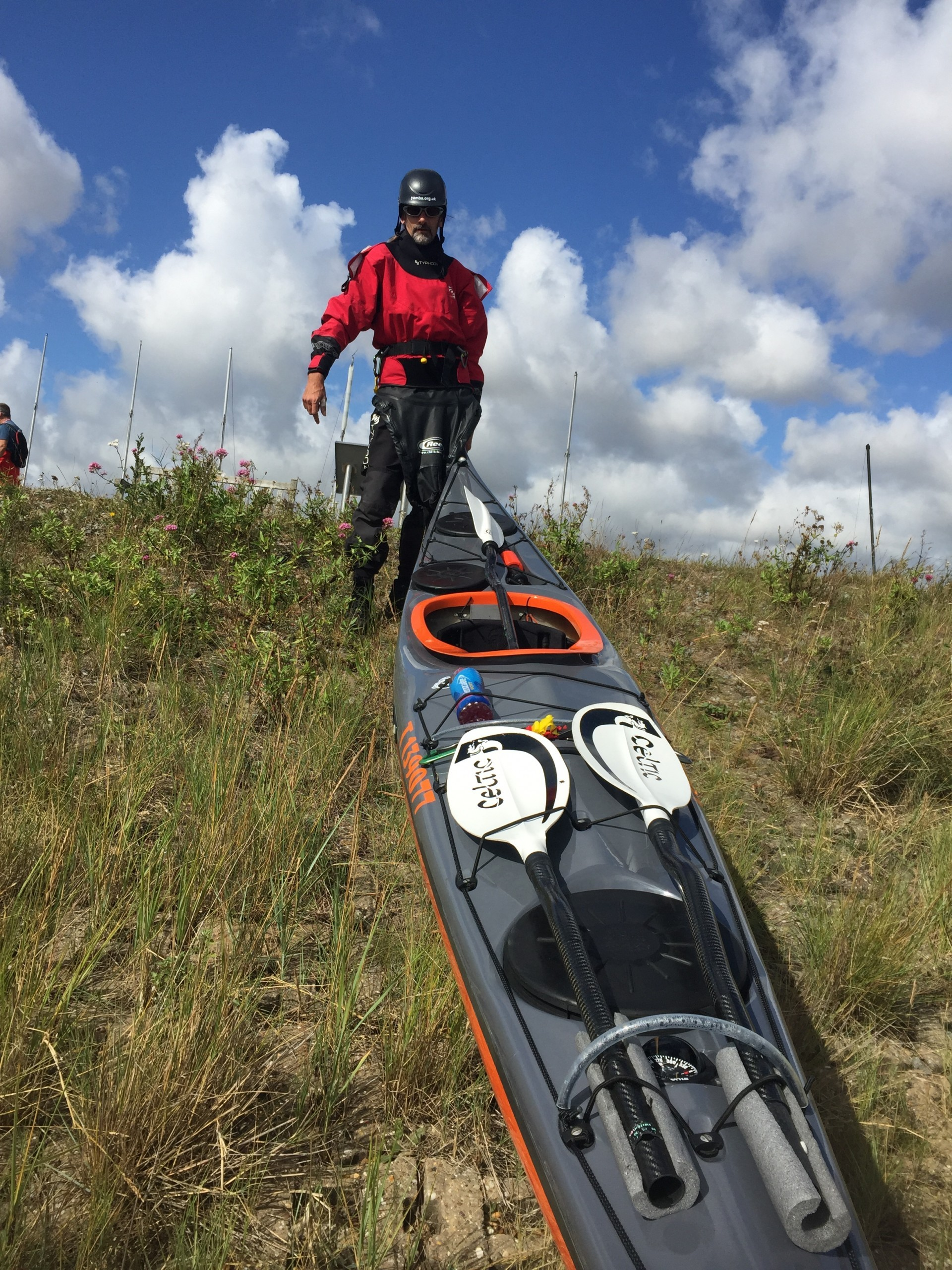 A sea kayak being carried down a grassy bank towards the ocean