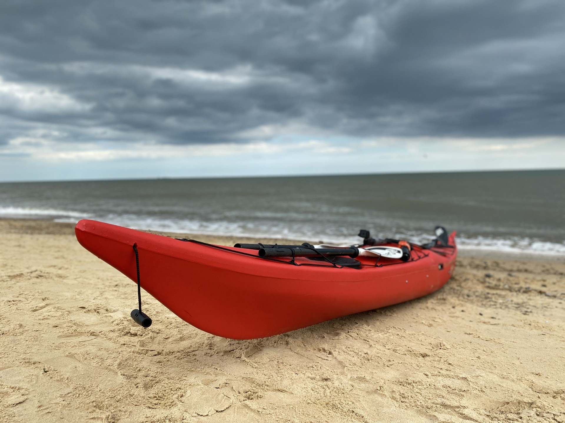 Red NDK roto-moulded sea kayak on a sandy beach