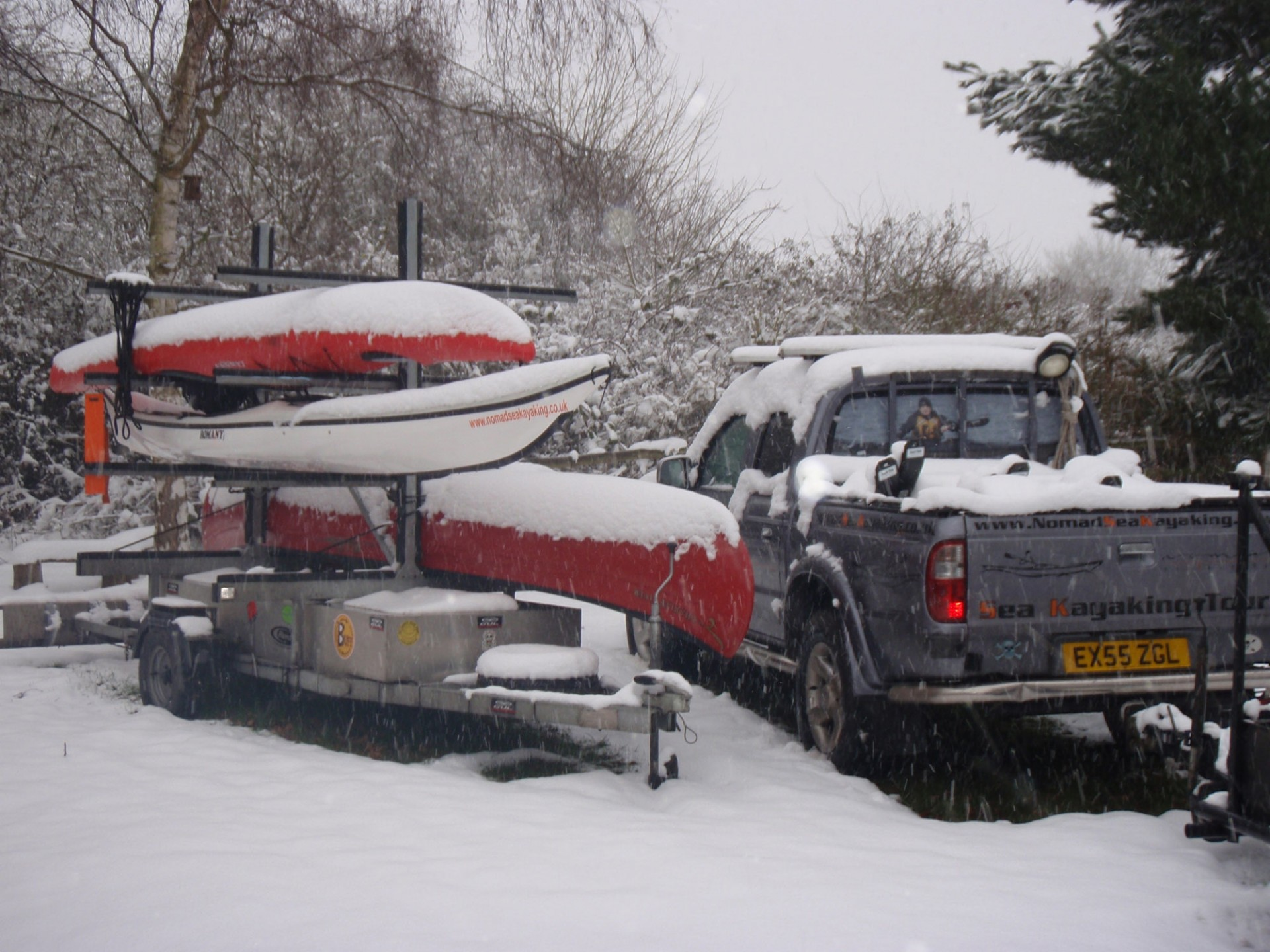 Kayaks on a trailer covered in snow