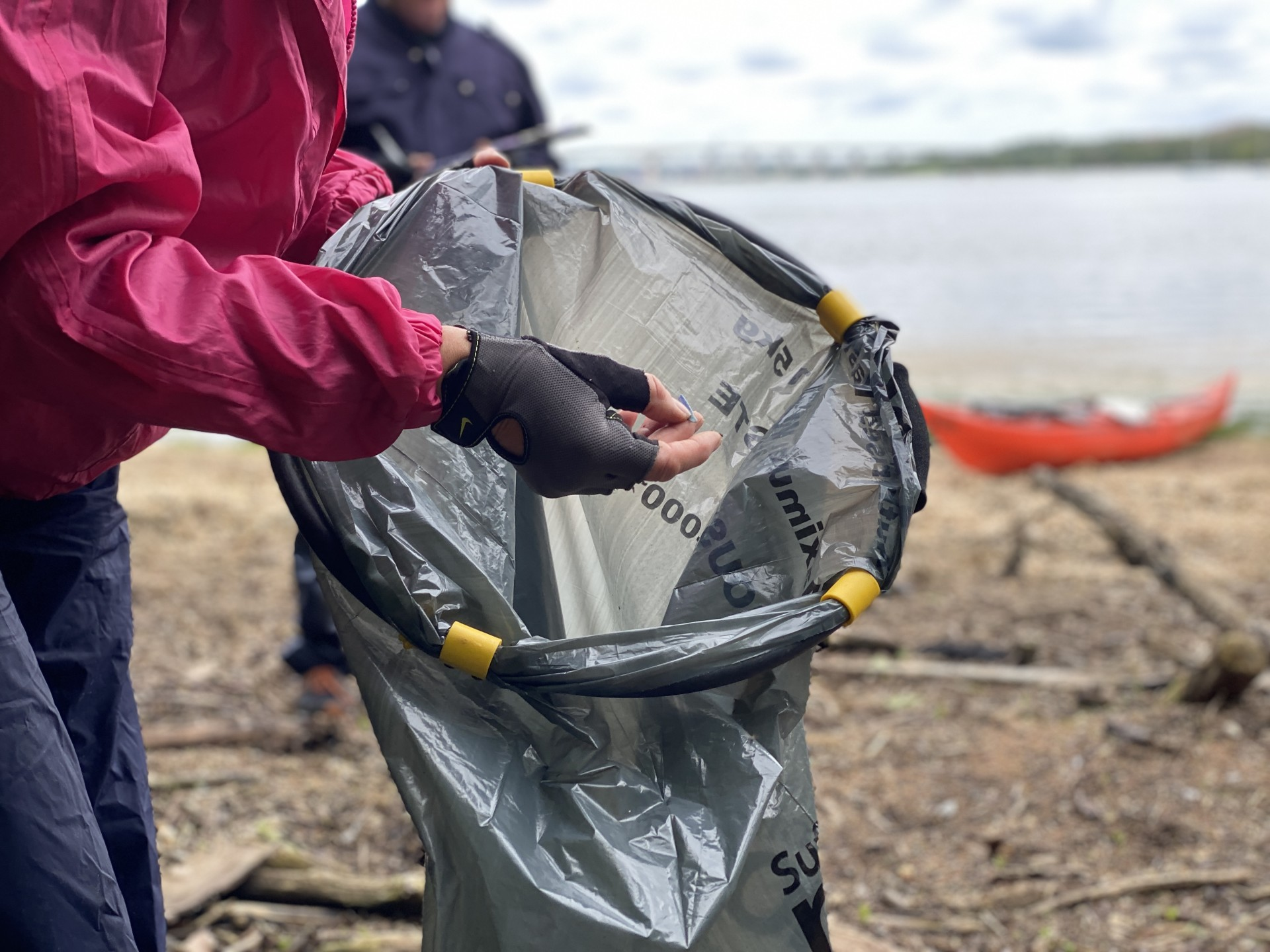 A black bin bag being filled with rubbish collected from a beach with kayaks in the background.