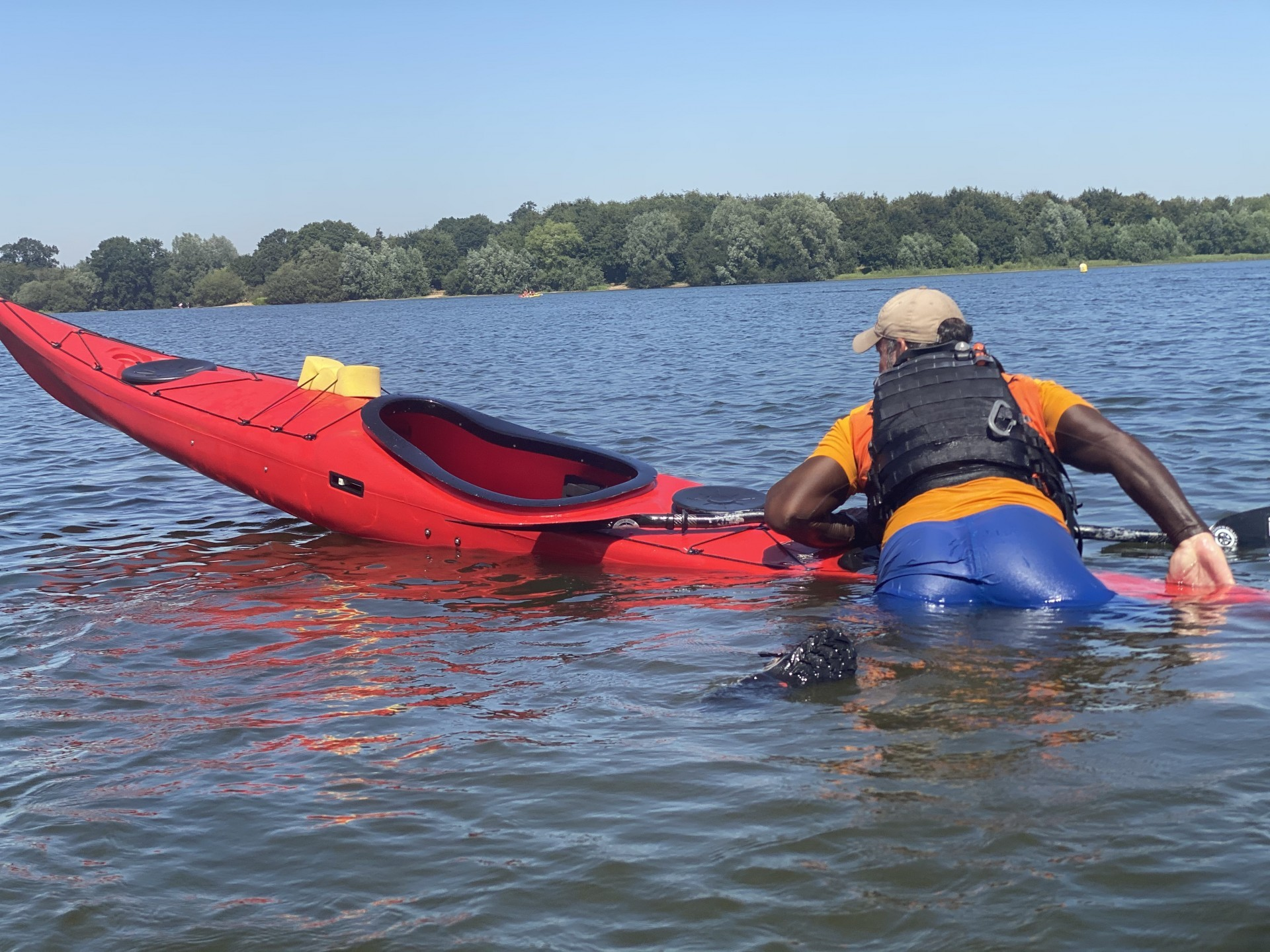 A paddler climbing onto the rear of a kayak whilst doing a self recovery during a training course